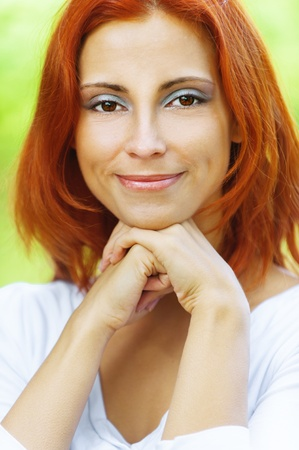 red head girl: Carroty beautiful woman propping up chin with his hands and smiling, on green park summer. Stock Photo