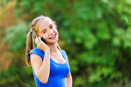 teenage girl dress: Smiling teenage girl in blue dress talking on cell phone, of green summer park.