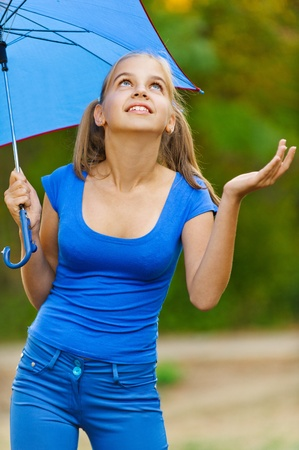 Teenager girl in blue dress holding an umbrella, and checks began to rain in summer green park. photo