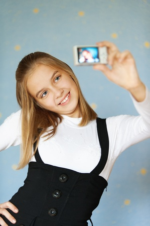 Beautiful blue-eyed girl-teenager photographed with camera itself, on blue background. photo