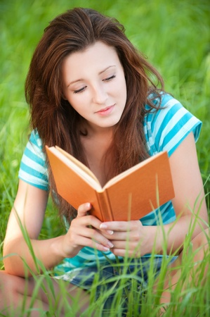 Portrait of beautiful young woman sits on grass and reading book at summer green park Stock Photo - 13082766