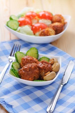 albondigas: close-up de gran variedad de deliciosas comidas, verduras picadas (pepinos, tomates), rebanadas de pastel de carne, mesa de cocina de madera con la servilleta, tenedor, cuchillo,