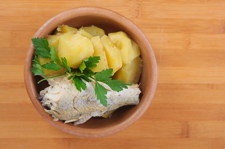 combo: Fish with boiled potatoes and parsley in a bowl on wooden table Stock Photo