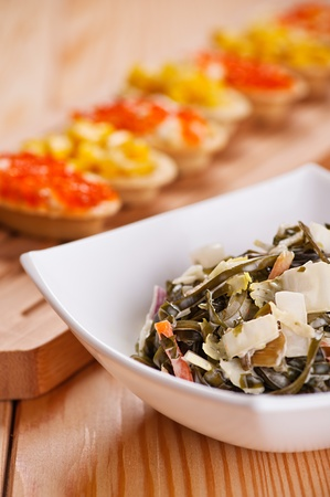 Tartlets with crab , corn salad and seaweed on wooden table. Stock Photo - 13082594