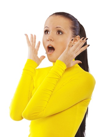 Portrait of shocked young beautiful woman in yellow turtleneck, who looks up, isolated on white background. photo