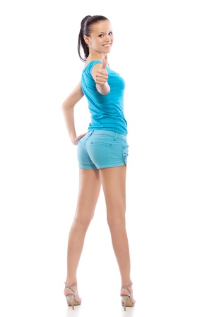 full height: Portrait of smiling young beautiful woman in blue blouse and shorts at full height raises the thumb, isolated on white background.