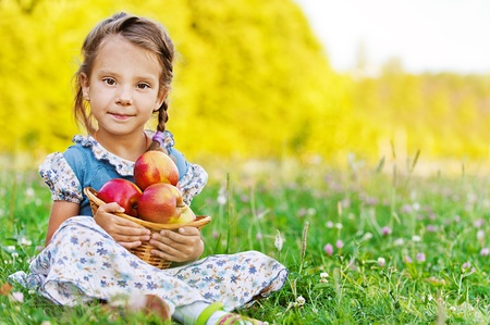 Beautiful little girl sitting on grass with basket of apples, against summer green of park. photo