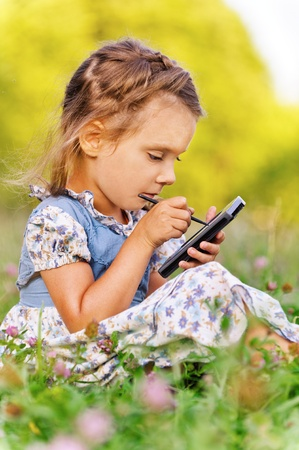 Beautiful little girl writes stylus on device, against summer green of park. photo