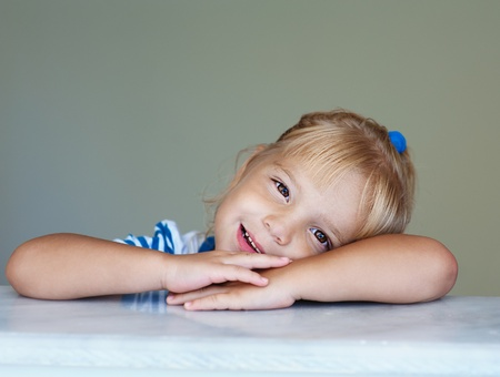 Beautiful little girl put her hands on marble railing and laughing. photo