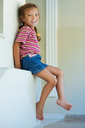 Beautiful little girl in shorts sitting on stone ledge, and laughs. photo