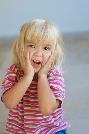suddenness: Beautiful blonde little girl in striped dress poses faces.