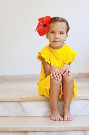 girl sit: Beautiful little girl in yellow dress with red flower sits on stone step.