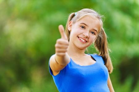 colegiala: Sonriendo adolescente en vestido azul muestra signo de la mano que lo está haciendo muy bien, contra el fondo del parque verde de verano. Foto de archivo