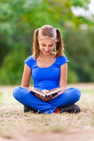 Smiling teenage girl in blue dress sitting in lotus position on green meadow in summer park and reading a book. Stock Photo - 13162830