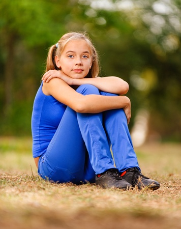 expect: Teenage girl in blue dress sitting on green meadow in summer park