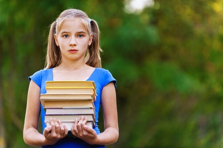 Teenager girl in blue dress holding stack of seven books in green summer park. photo