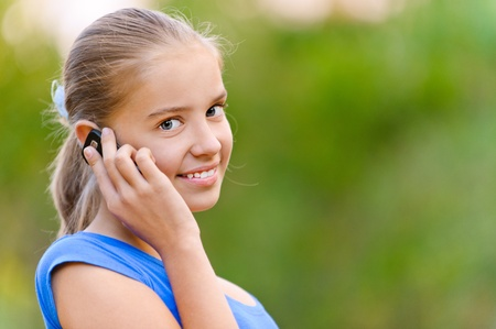 phone calls: Smiling teenager girl in blue dress talking on cell phone in green summer park.