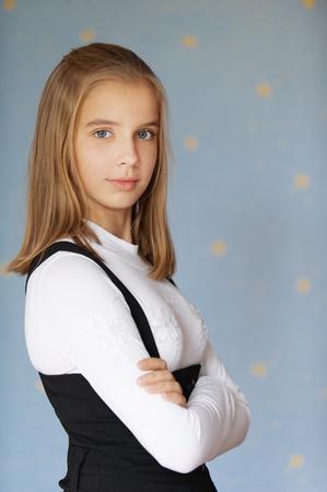 colegiala: Hermosa niña de ojos azules-adolescente con los brazos cruzados, sobre fondo azul.