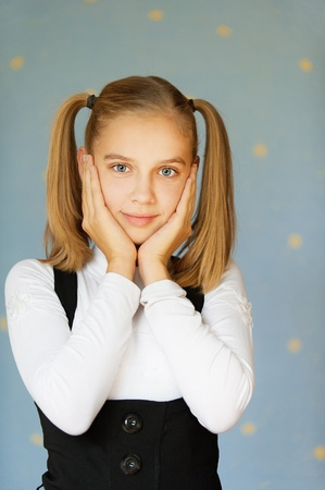 schoolgirl uniform: Beautiful blue-eyed girl-teenager grabbed his cheeks with his hands, on blue background.