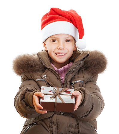 orchestration: Beautiful little girl in warm winter jacket and red hat with Christmas gift, isolated on white background.
