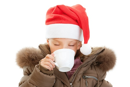 orchestration: Beautiful little girl in warm winter jacket and red Christmas hat drink tea, isolated on white background.