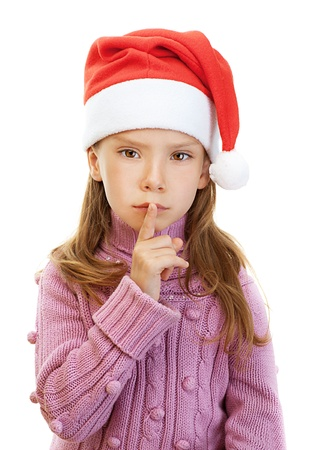 Beautiful little girl in pink sweater and red Christmas hat put finger to his lips, isolated on white background. photo