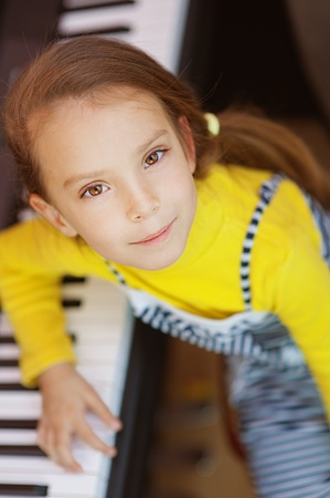 upright piano: Beautiful little girl in yellow dress plays piano.