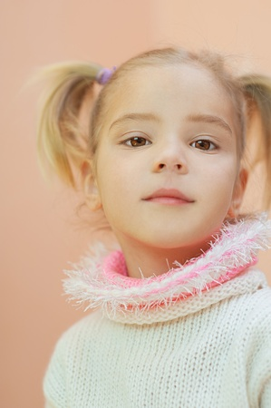 Portrait of beautiful blonde little girl in white sweater. photo