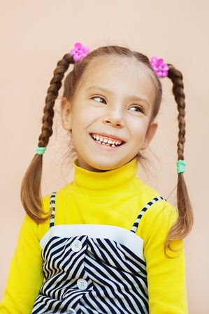 aslant: Beautiful little girl in yellow dress with pigtails looks askance, and laughing merrily.