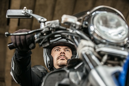 Dark-haired man sitting sitting on his motorcycle. Stock Photo - 13318873