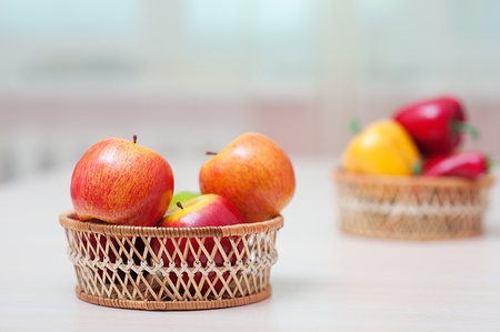 viands: Baskets with ripe red apples, and bell pepper on table against the window.