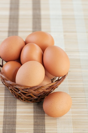 Wicker basket with chicken eggs on table with striped tablecloth. photo
