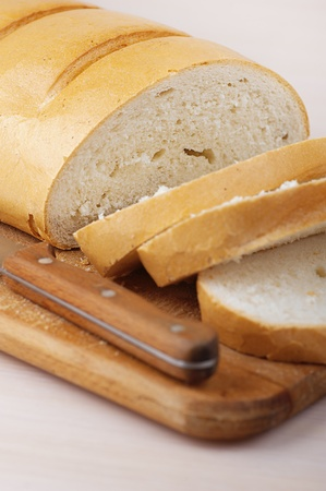 farinaceous: Cut loaf of white bread and knife is close up on breadboard.