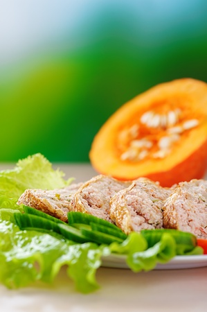 viands: Meat dish with lettuce on background of pumpkin and green summer garden. Stock Photo