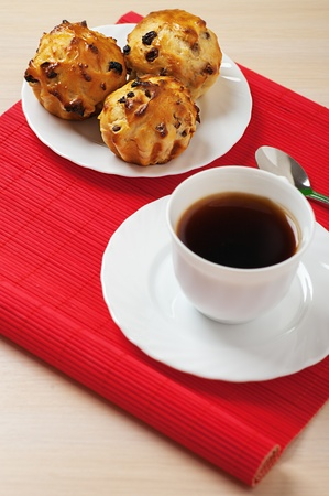 viands: Small muffins on plate and cup of tea on red bamboo table cloth.