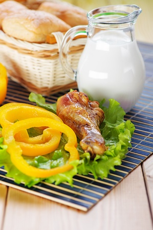 viands: Fried chicken drumstick with green leaf lettuce and yellow bell pepper, milk jug and basket of bread on wooden rustic table. Stock Photo