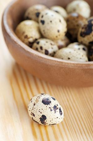 huevos de codorniz: Huevos de codorniz en un tazón en la mesa de madera.