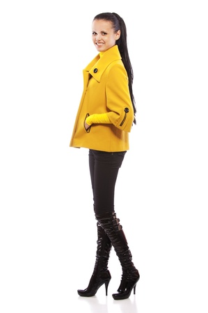 full height: Portrait of smiling young beautiful woman in yellow coats at full height, isolated on white background. Stock Photo