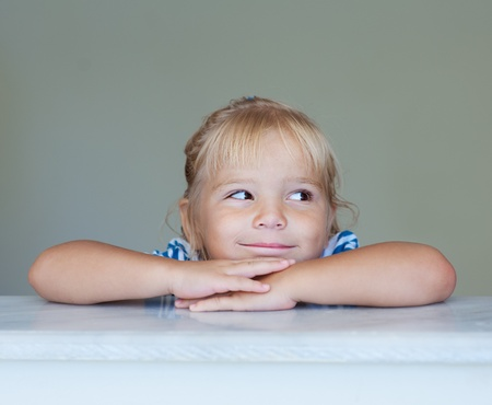 aslant: Beautiful little girl put her hands on marble railing and laughing. Stock Photo