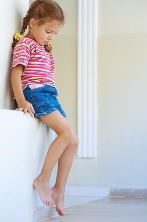Beautiful little girl in shorts sitting on stone ledge, and sad.