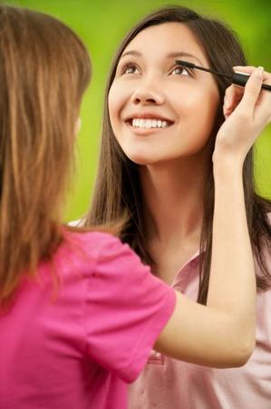 Two teenage girls dye their eyelashes background summer nature photo