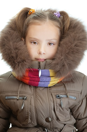 orchestration: Beautiful little girl closeup in warm winter jacket and scarf, isolated on white background.