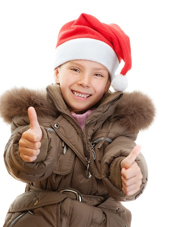 orchestration: Beautiful little girl in warm winter jacket and red Christmas hat shows finger as sign that everything is fine, isolated on white background.