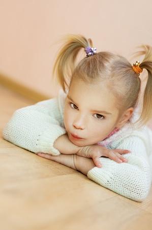 Beautiful sad little girl in white sweater on floor. Stock Photo - 13379441