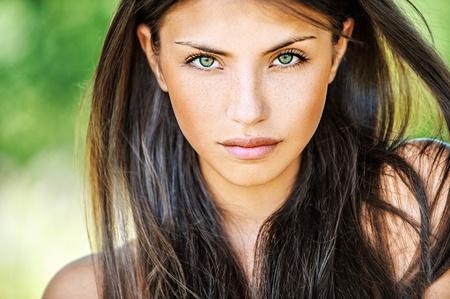 ojos verdes: Close up retrato de mujer joven y hermosa, en la naturaleza verde de verano, de fondo.