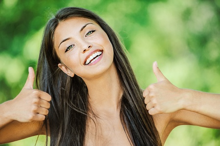 Portrait of young beautiful woman with bare shoulders happily raises his thumb up and smiling, on green background summer nature. photo