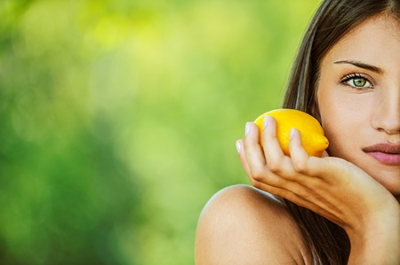 viands: Portrait half of face young beautiful woman with bare shoulders holding lemon yellow, on green background summer nature.