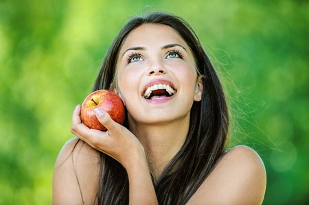 bare shoulders: Portrait of young beautiful woman with bare shoulders holding an red apple and smiling, on green background summer nature.