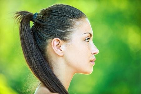 Portret profiel van het gezicht van jonge mooie vrouw, op groene achtergrond zomer natuur. Stockfoto