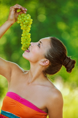 viands: Portrait of young beautiful woman with bare shoulders holding grapes, on green background summer nature.